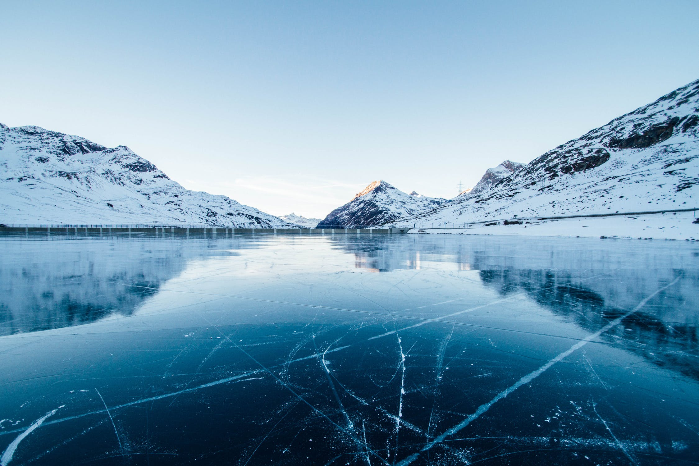 Ice covered lake surrounded by snowy mountains