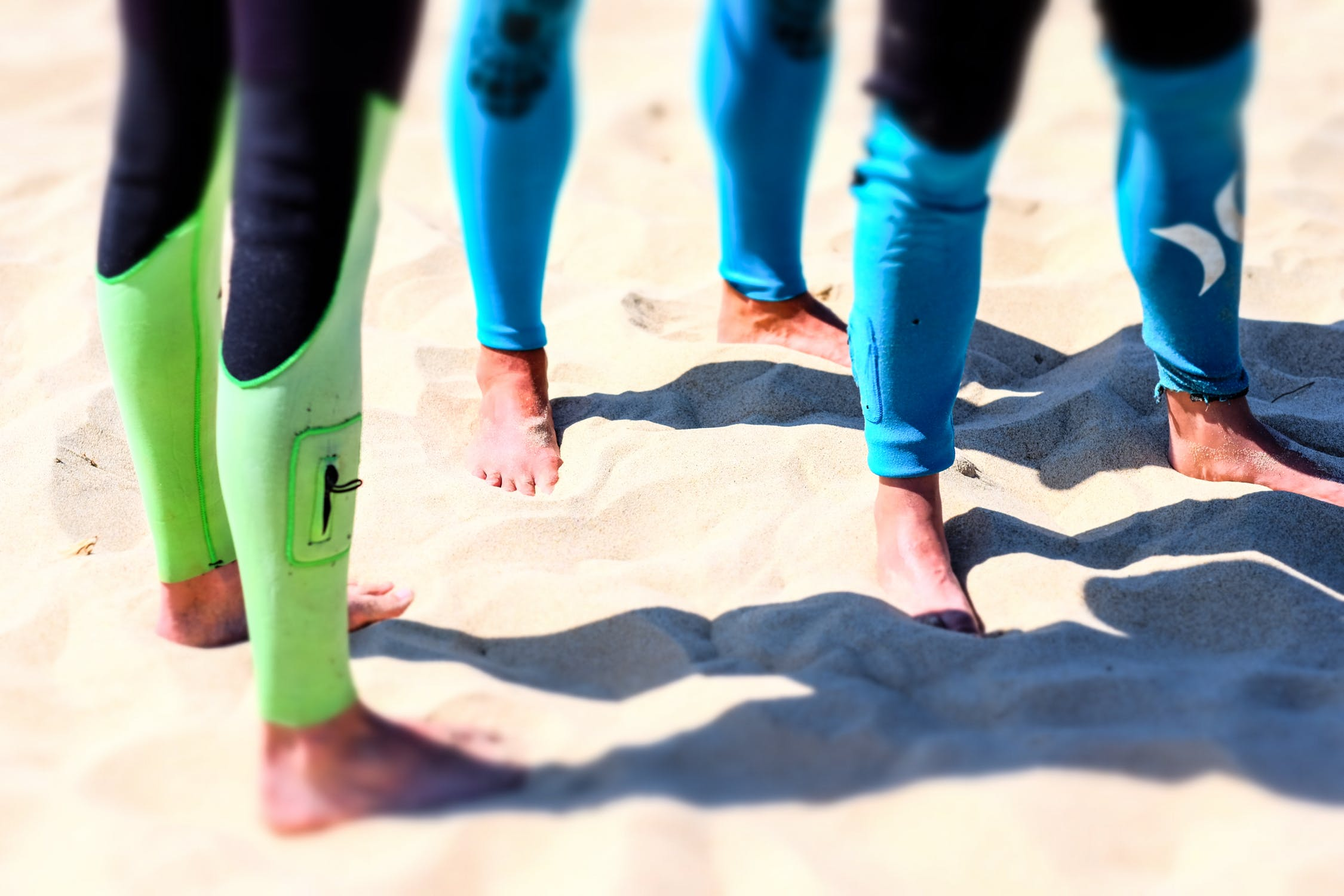 People wearing wetsuits on the beach